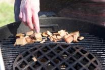 Rozpálíme si gril a po okrajích roštu poklademe namočené udící lupínky.