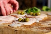 Na plátky šunky pokládáme zelené olivy.