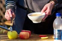 Na dno jablek dáme lžičku drcených sušenek.