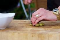 Při krájení oliv dbáme na to, abychom měli kousky stejnoměrné. U plněných oliv vmícháme i nasekanou papričku, která tvoří náplň olivy. Pro obměnu můžeme použít i další druhy oliv.