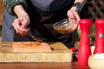 K potírání filetu použijeme silikonový štětec nebo pouze lžičku. Potřený filet lososa odložíme stranou. Vyjmeme z vody cedrové prkénko a lehce ho osušíme.