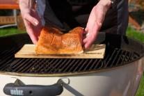 Rybu opatrně přeneseme rukami nebo lopatkou na ryby Weber style. Pro silnější aroma můžeme na rozžhavené brikety vhodit ještě 1 - 2 hrsti namočených cedrových lupínků.