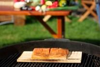 Cedrové lupínky je možné položit suché i na rozpálený grilovací rošt kolem prkénka s rybou. Přiklopíme víkem grilu a necháme udit.