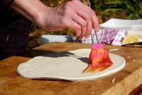 Těsto přesuneme na kovový tác a potřeme jej rajčatovou směsí.