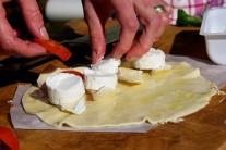 Polovinu kruhu potřeme rajčatovou omáčkou a poklademe na ní sýr nakrájený na kousky.