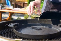 Do grilu Weber One-Touch jsme použili těžkou litinovou pánev BBQ. Na pánev nalijeme trochu oleje a necháme řádně prohřát. Zkoušku teploty provedeme vhozením jednoho kousku do oleje na pánvi. Pokud se začne hned smažit, je olejdost rozehřátý a my můžeme přidat ostatní naložené maso.