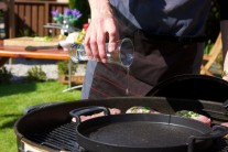 Doprostřed grilu umístíme litinovou pánev s trochou oleje. Jarní cibulky nasekáme nadrobno a nasypeme do pánve, podusíme a po chvíli přidáme kukuřičná zrnka.
