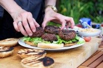 Rozpečenou housku pomažeme podle chuti kečupem, hořčičí nebo majonézou, přidáme ledový salát, maso...
