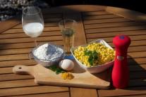 K přípravě kukuřičných placiček si připravíme zrnka kukuřice - mražené nebo čerstvé, mléko, mouku, vejce, sůl, kari koření, červenou kapii,  zelené čerstvé bylinky a trochu oleje na smažení.