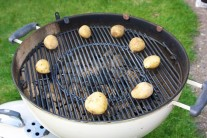 Brambory vložíme na rošt grilu a přiklopené grilujeme 30 minut, dokud nejsou brambory měkké. Občas zkontrolujeme a obrátíme nebo přesuneme na okraj grilu či zpět na střed. V našem případě byl použit gril Weber One-Touch Premium 57.