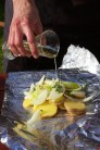Naskládané brambory s cibulí, osolené a opepřené zakápneme olejem. Můžeme přidat ještě aromatické zelené bylinky jako tymián a rozmarýn, které dodají bramborám intenzivní vůni.