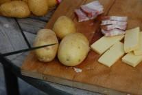 Nyní nařízneme brambory tak, aby se do vzniklého prostoru dala zasunout slaninka a sýr.