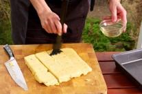 Polentu dáme do mělkého pekáče, přikryjeme alobalem nebo potravinářskou fólií a necháme tak na 4 hodiny vychladnout. Vychladlou polentu nakrájíme na stejně velké kusy a potřeme jí olivovým olejem.