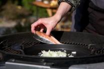 Ve chvíli, kdy žačneme smažit cibulku, přidáme utřený nebo prolisovaný česnek. Zároveň položíme na rozpálený grilovací rošt porce lososa a grilujeme z každé strany po dobu 6 minut.
