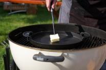 Do středu kotlového grilu na dřevěné uhlí Weber One-Touch Premium  jsme umístili těžkou litinovou pánev BBQ, na které jsme rozehřáli kvalitní máslo.