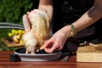 Naplněné kuře s máslem opatrně přeneseme na stojan na grilování drůbeže Weber . Vložíme do grilu na středním žáru grilujeme po dobu přibližně 1a1/2 hodiny. Kuře kontrolujeme, průběžně potíráme zachycenou vypečenou šťávou. Můžeme potírat i pomerančovou šťá
